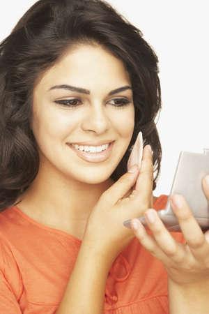 relishing: Hispanic woman applying make up LANG_EVOIMAGES