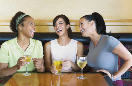 wooing: Three women laughing and having cocktails