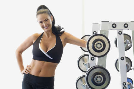 free weights: Portrait of woman next to rack of free weights