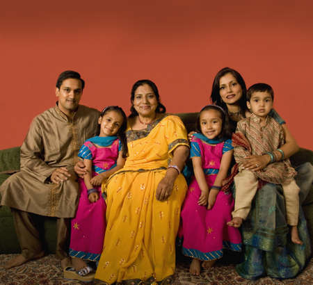 family sofa: Multi-generational Indian family in traditional dress