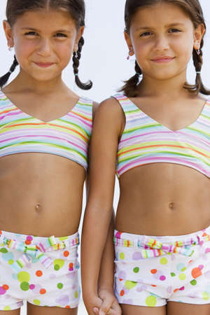 bathing suits: Hispanic sisters wearing matching bathing suits LANG_EVOIMAGES