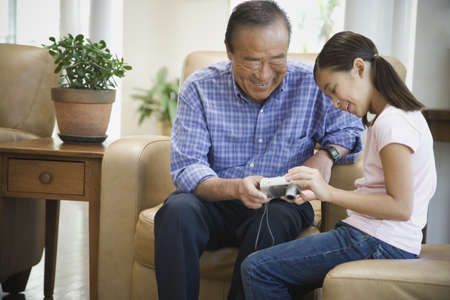 gramma: Asian grandfather and granddaughter looking at digital camera LANG_EVOIMAGES