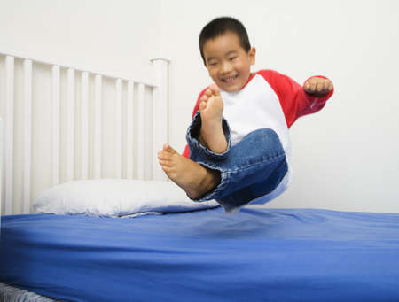 Asian boy jumping on bed