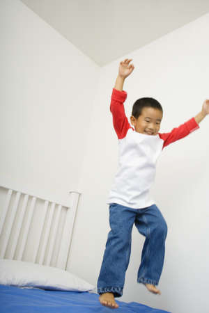 tot: Asian boy jumping on bed