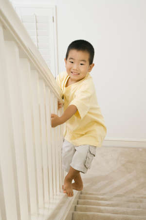fathering: Asian boy climbing banister of staircase