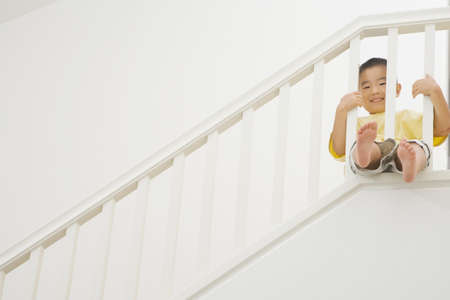 jeopardizing: Asian boy with legs through railing of staircase LANG_EVOIMAGES