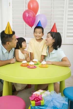 relishing: Asian boy celebrating birthday with family LANG_EVOIMAGES