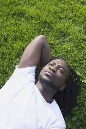 African man laying in grass