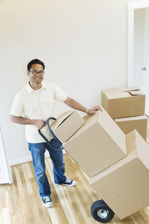 casualness: Asian man moving boxes in new house LANG_EVOIMAGES