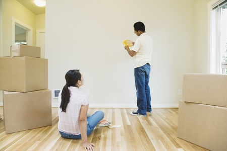 go inside: Asian couple looking at paint swatches in new house