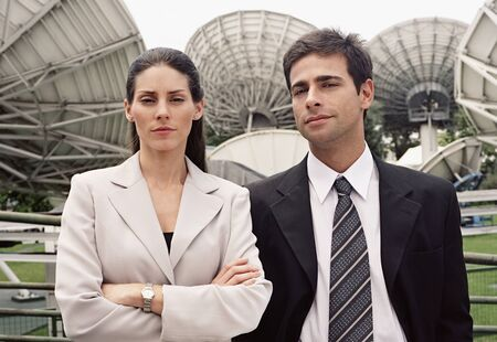 commercialism: Portrait of Hispanic businesspeople in front of satellite dishes