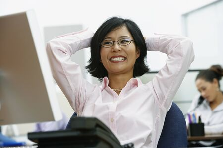 arms behind head: Portrait of Asian businesswoman with arms behind head