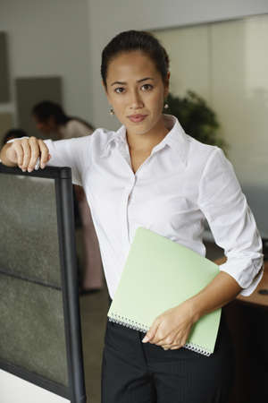 cubicle: Asian businesswoman leaning on cubicle wall