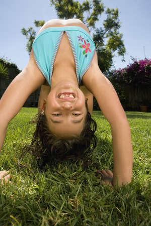 low spirited: Hispanic girl doing back bend in grass