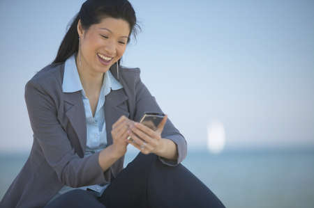 finding a mate: Asian woman using electronic organizer outdoors