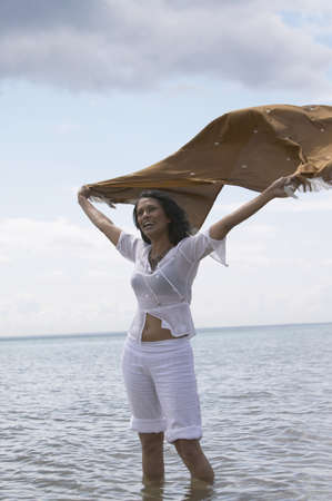 nite: Woman standing in water with shawl flowing out behind her LANG_EVOIMAGES