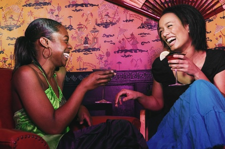 alehouse: Two African women holding cocktails and laughing