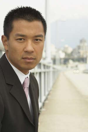 stepping: Portrait of Asian businessman on urban bridge