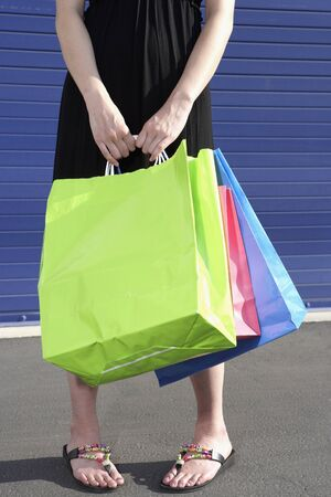 unconcerned: Close up of woman holding shopping bags LANG_EVOIMAGES