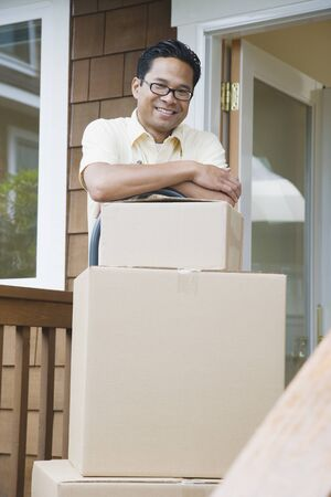 flogging: Asian man leaning on moving boxes on porch
