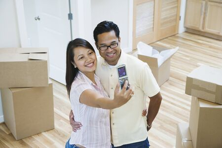 shopping buddies: Asian couple taking own photograph in new house