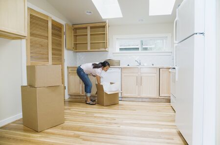 Asian woman unpacking boxes in new house Stock Photo