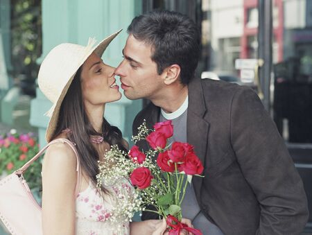 Hispanic couple kissing and holding flowers