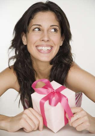 pacific islander ethnicity: Portrait of Hispanic woman holding gift