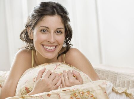 casualness: Portrait of Hispanic woman laying on bed