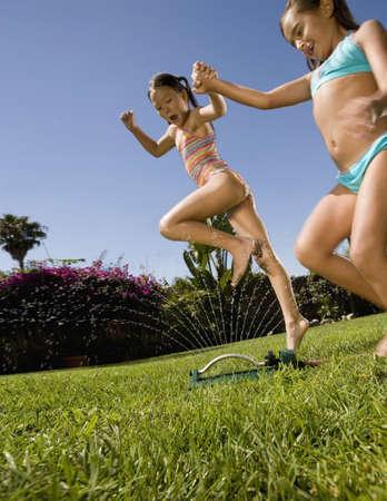 saturating: Two girls jumping over lawn sprinkler LANG_EVOIMAGES