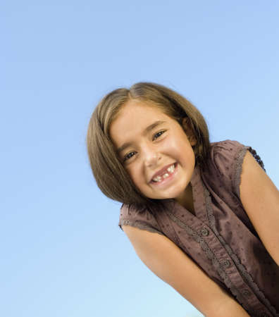 elementary age girl: Portrait of Hispanic girl under blue sky LANG_EVOIMAGES
