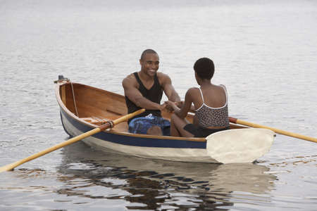 searcher: African couple smiling in row boat LANG_EVOIMAGES