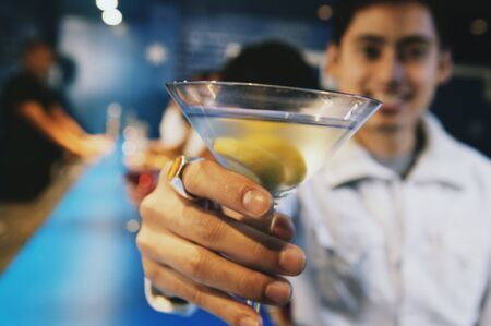 Pacific Islander man toasting with cocktail at bar Stock Photo