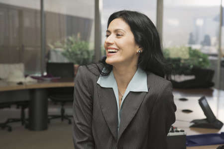 daydreamer: Portrait of Hispanic businesswoman laughing LANG_EVOIMAGES