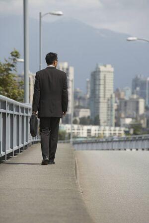 wearying: Asian businessman walking on urban bridge