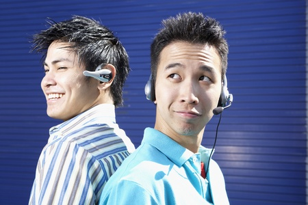 blabbing: Two young men back to back wearing headsets LANG_EVOIMAGES