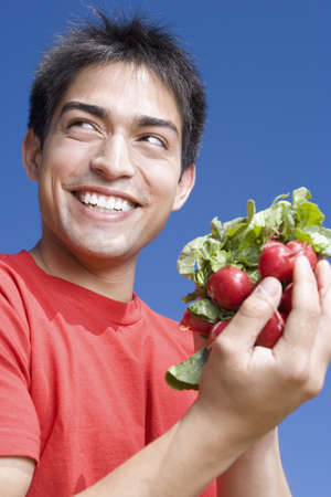 Pacific Islander man holding bunch of radishes