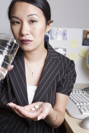 joining forces: Asian businesswoman taking medication at desk