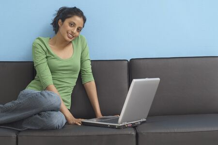 casualness: Portrait of Middle Eastern woman with laptop