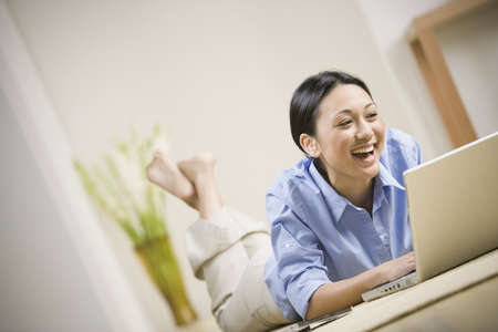 asian bowl: Pacific Islander woman laying on floor using laptop