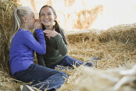 casualness: Two girls sitting in hay telling secrets