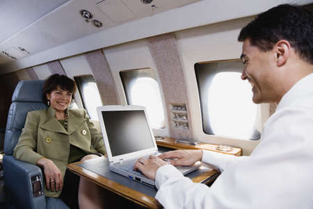 private: Businessman and businesswoman with laptop on private airplane