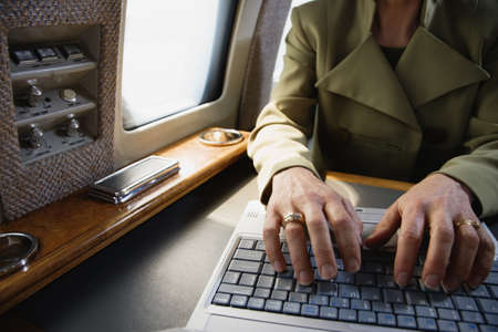 Close up of businesswoman using laptop on private airplane Stock Photo