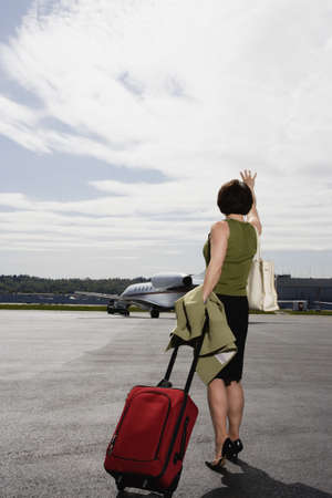 pacific islander ethnicity: Businesswoman with suitcase waving on tarmac