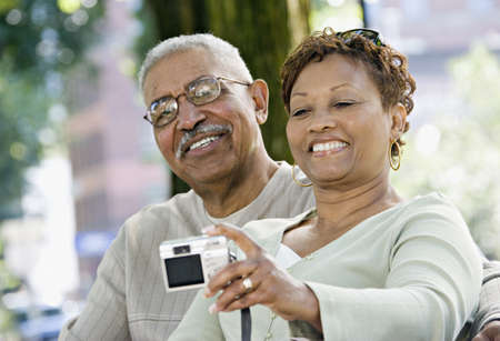 fathering: Senior African couple taking self-portrait in park