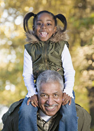 mature old generation: African grandfather carrying granddaughter on shoulders