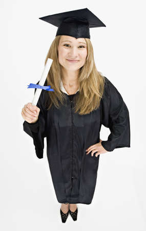 motioning: Studio shot of young woman in graduation cap and gown