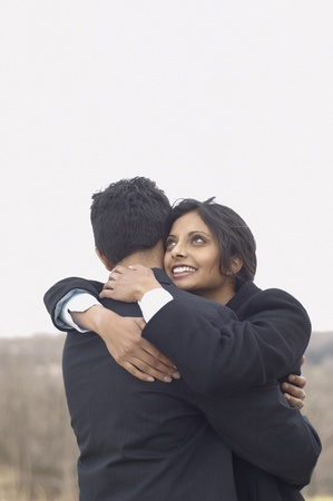 hugging couple: Portrait of couple hugging outdoors LANG_EVOIMAGES