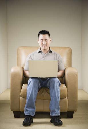 motioning: Asian man using laptop in armchair