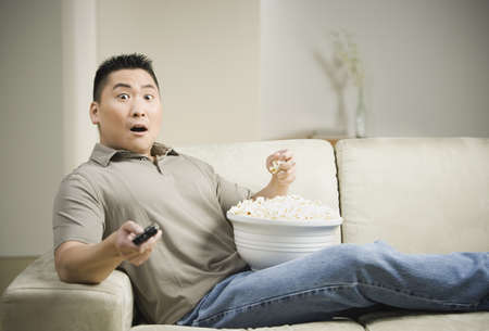 casualness: Asian man eating popcorn on sofa with remote control